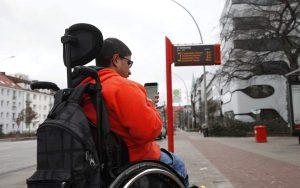 Junger Mann im Rollstuhl und Smartphone in der Hand