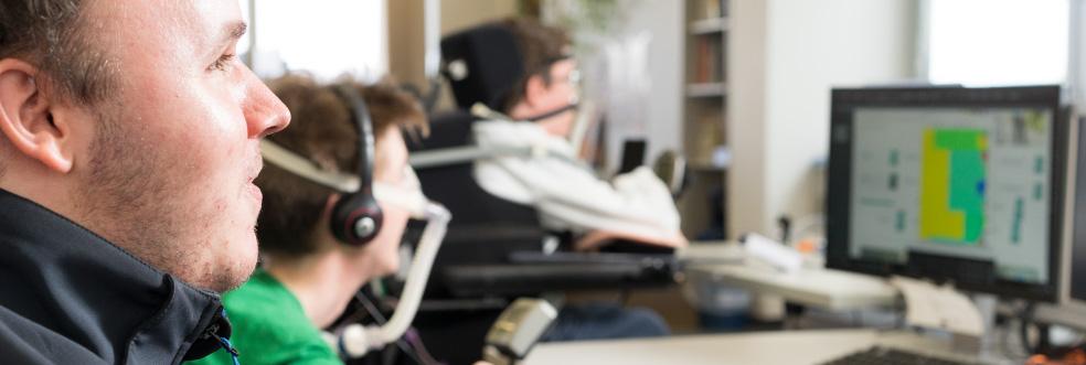 Mehrere Menschen sitzen mit Headsets vor Computerbildschirmen.